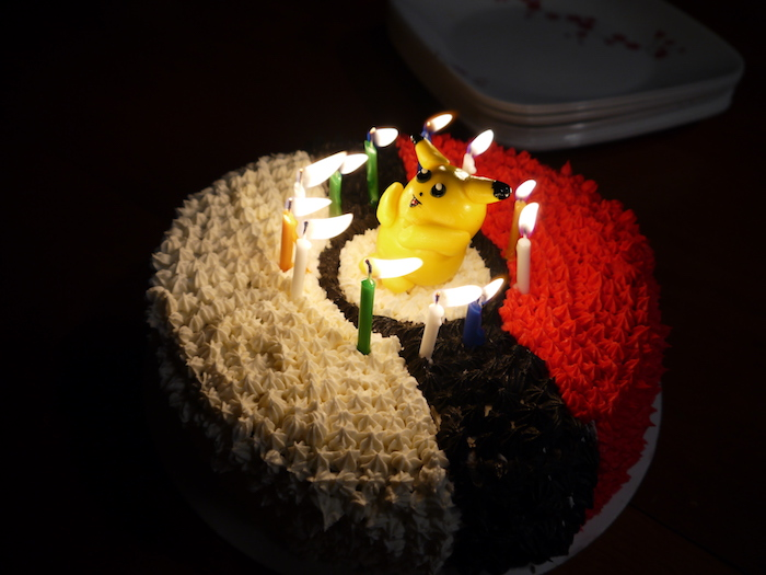 gateau pokemon, figurine pikachu en plastique, bougies d'anniversaire, crème blanche, balle de pokémon