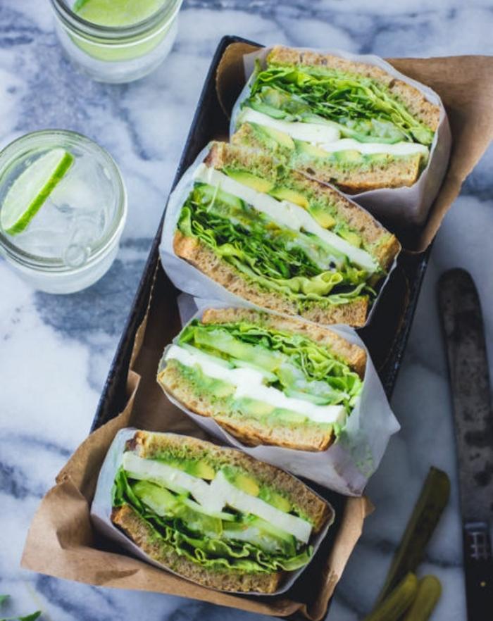 sandwich à la mayonnaise, ail, citron, herbes fraîches, tomate verte zebrée, mozzarella entre deux tranches de pain complet dans des sachets