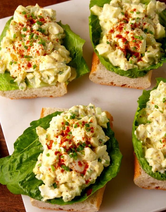 salade picnic aux oeufs, mayonnaise et moutarde dans une feuille de laitue, gariture de ciboulette et paprika sur une tranche de baguette
