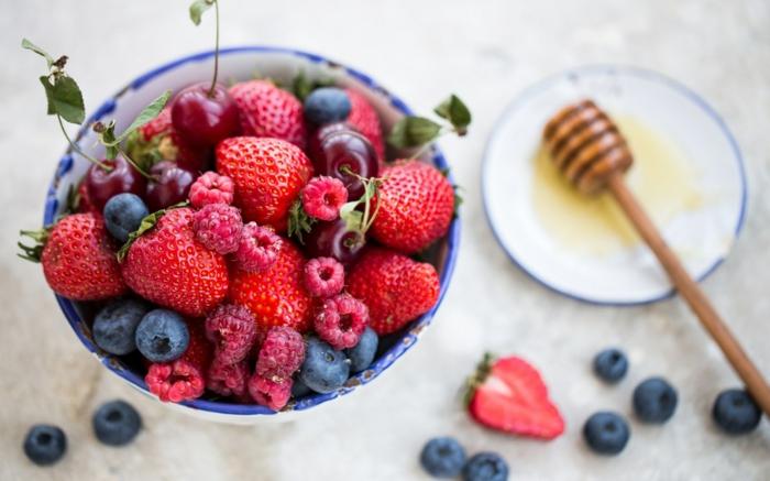 dessert sain, fraises, framboises, myrtilles, bol blanc et vert, miel, assiette plate, cerises, comptoir en marbre