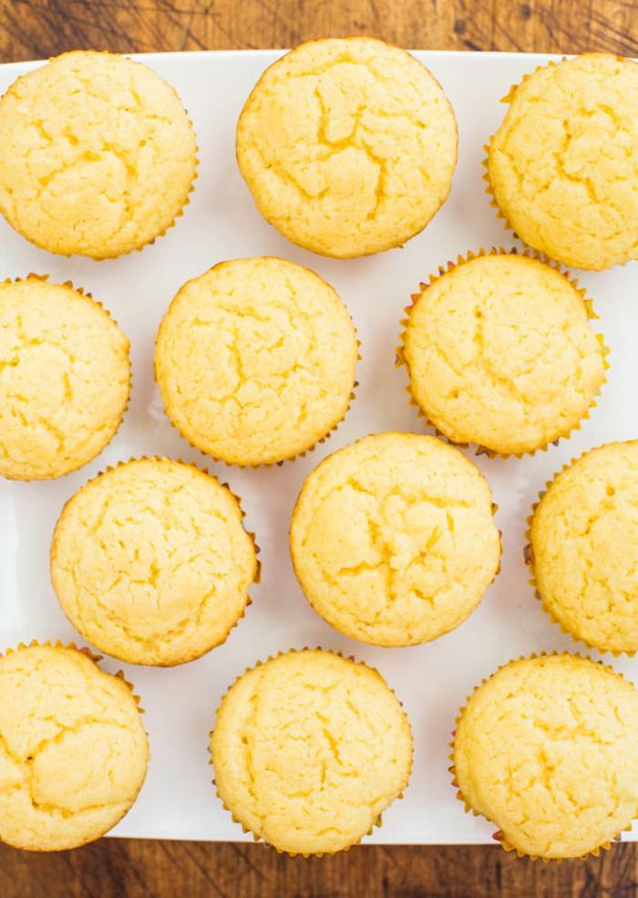 recette dietetique, muffins à la vanille, dessert jaune, papier blanc, table en bois, caissette en papier jaune