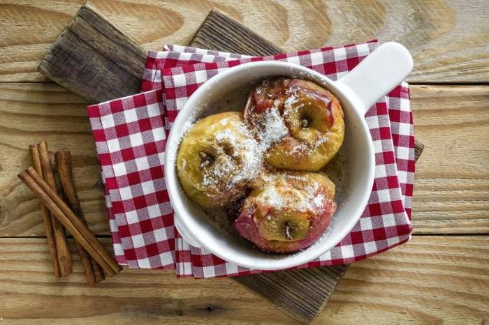 dessert peu calorique, serviette carrée en blanc et rouge, table en bois, bâtons de cannelle, pommes au four