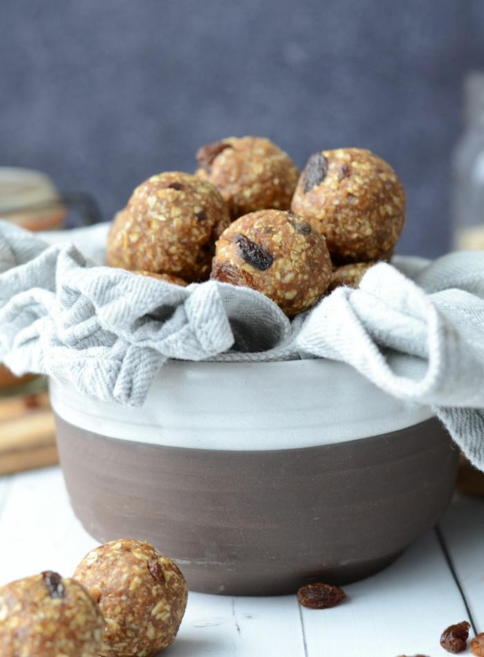 recette dietetique, serviette blanche, bol taupe, table en bois blanche, boules en avoine