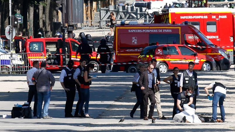 La police criminelle inspecte les lieux de l'attentat, lundi sur les Champs-Élysées, et recouvre le corps de l'assaillant.