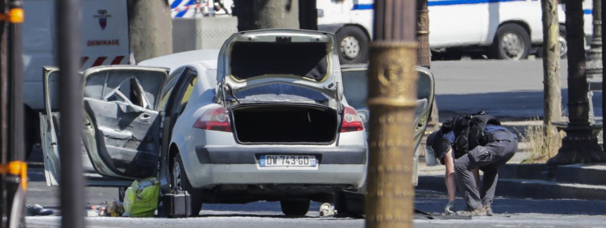 Un agent des forces de l'ordre se trouve à proximité de la voiture avec laquelle un homme a percuté un fourgon de gendarmerie, sur les Champs-Elysées, à Paris, le 19 juin 2017. (THOMAS SAMSON / AFP)